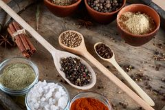Various spices in wooden spoons and bowls and some salt on an old wooden barrel, top view, close-up, selective focus. Various spices in wooden spoons and bowls Royalty Free Stock Image