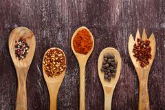 Various spices in wooden spoons on dark brown background. Different types of paprika and peppercorn. Top view stock photos