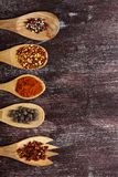 Various spices in wooden spoons on dark brown background. Different types of paprika and peppercorn. Top view. Copy space stock images