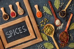 Various spices in wooden spoons on dark stone table. Various indian spices in wooden spoons, seeds, herbs on dark stone table. Colorful spices, top view royalty free stock images