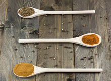 Various spices on wooden spoons and vintage wooden background stock image