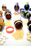 Various spilled medicines. A collection of spilled medicines (gelcaps, tablets, vitamins) and their bottles Stock Photos
