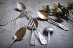 Various spoons and forks entwined on rustic wooden table Royalty Free Stock Photos