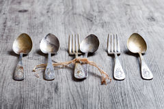 Various spoons and forks entwined on rustic wooden table Stock Images