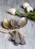 Various spoons and forks entwined on rustic wooden table Stock Photos