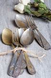 Various spoons and forks entwined on rustic wooden table royalty free stock photography