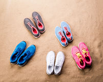 Various sports shoes laid on sand beach, studio shot Royalty Free Stock Images