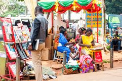 Various stalls on Kampala Road sidewalk, Uganda. Newspaper and stationary stand and cell phone kiosk on sidewalk, Kampala Road, Kampala, Uganda stock images