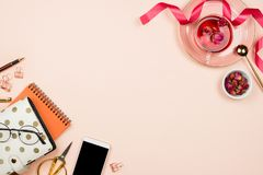 Various stationary accessories on pastel background. Glasses, clips, planner, scissors, smartphone, tea in a glass cup, pink ribbon, golden spoon, flatlay Royalty Free Stock Photos