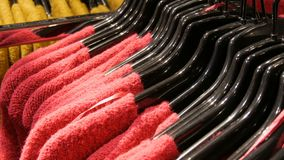 Various stylish knitted multicolored sweaters hanging on fashion black hangers in a clothing store in mall or shopping stock footage