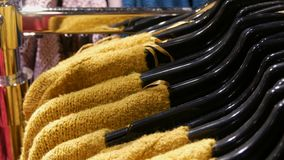 Various stylish knitted multicolored sweaters hanging on fashion black hangers in a clothing store in mall or shopping. Various stylish knitted multicolored stock video