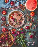 Various summer berries and fruits on rustic aged kitchen table with flowers and plates, top view, flat lay royalty free stock photography