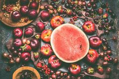 Various summer berries and fruits: watermelon, strawberries, peaches, plums, cherries, gooseberries, currants on rustic kitchen t. Able with flowers and plates royalty free stock photos