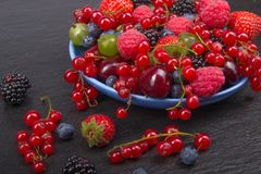Various summer Fresh berries in a bowl on rustic wooden table. Antioxidants, detox diet, organic fruits. Various summer Fresh berries in a bowl on rustic wooden Royalty Free Stock Photography