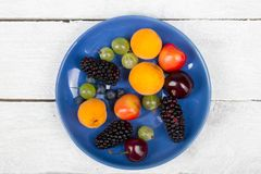 Various summer Fresh berries in a bowl on rustic wooden table. .Antioxidants, detox diet, organic fruits. Top view. Various summer Fresh berries in a bowl on Royalty Free Stock Photos
