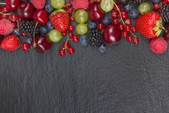 Various summer Fresh berries in a bowl on rustic wooden table. Antioxidants, detox diet, organic fruits. Top view. Various summer Fresh berries in a bowl on Stock Photos