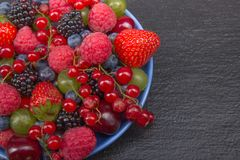 Various summer Fresh berries in a bowl on rustic wooden table. Antioxidants, detox diet, organic fruits. Various summer Fresh berries in a bowl on rustic wooden Royalty Free Stock Image