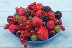 Various summer Fresh berries in a bowl on rustic wooden table. Antioxidants, detox diet, organic fruits. Various summer Fresh berries in a bowl on rustic wooden Stock Photos