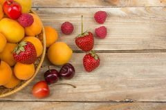 Various summer Fresh berries in a bowl on rustic wooden table. .Antioxidants, detox diet, organic fruits. Royalty Free Stock Photo