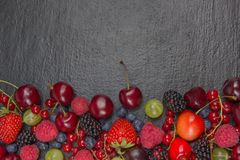 Various summer Fresh berries in a bowl on rustic wooden table. Antioxidants, detox diet, organic fruits. Top view. Various summer Fresh berries in a bowl on Stock Photo