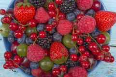 Various summer Fresh berries in a bowl on rustic wooden table. Antioxidants, detox diet, organic fruits. Top view Stock Photo