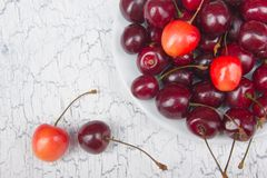 Various summer Fresh Cherry in a bowl on rustic wooden table. Antioxidants, detox diet, organic fruits. Top view Royalty Free Stock Photos
