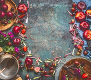 Various summer fruits and berries: strawberries, peaches, plums, cherries, gooseberries and currants on rustic kitchen table. With cooking pot and spoon, top royalty free stock photo
