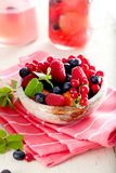 Various summer fruits in a bowl. Assorted fresh berries with lea. Ves on wooden background stock photos