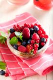 Various summer fruits in a bowl. Assorted fresh berries with lea. Ves on wooden background stock image