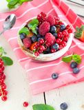 Various summer fruits in a bowl. Assorted fresh berries with lea. Ves on wooden background royalty free stock photos