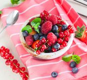 Various summer fruits in a bowl. Assorted fresh berries with lea. Ves on wooden background stock images