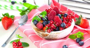 Various summer fruits in a bowl. Assorted fresh berries with lea. Ves on wooden background royalty free stock images
