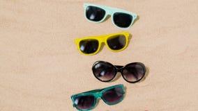 Various sunglasses on beach sand stock footage