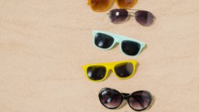 Various sunglasses on beach sand stock video