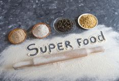 Various Superfoods and the inscription `Super food` on a grey table. Background of baking with natural additives to flour. stock photography