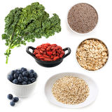 Various Superfoods Isolated on White. Includes kale, chia seeds, goji berries, blueberries, oats and quinoa Royalty Free Stock Photography