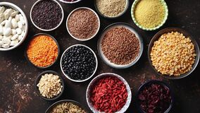 Various superfoods in smal bowls on dark rusty background