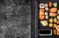 Various sushi on black wooden plate on rustic grunge background, top view Stock Image