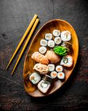 Various sushi and rolls on a plate with sticks. On dark rustic background stock photography