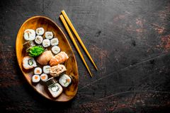 Various sushi and rolls on a plate with sticks. On dark rustic background royalty free stock photography