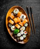 Various sushi rolls with salmon and vegetables on a wooden plate with chopsticks. On black rustic background stock photo