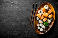 Various sushi rolls with salmon and vegetables on a wooden plate with chopsticks. On black rustic background stock photos
