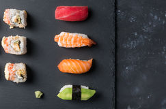 Various sushi and rolls with wasabi on slate plate and black stone table. Free space and top view Stock Images