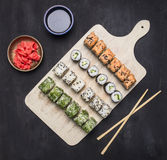 Various sushi sets, dill, salmon, crab on a white cutting board  Asian food on wooden rustic background top view close up Royalty Free Stock Photos