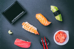 Various sushi on slate plate with chopsticks, wasabi, ginger and soya sauce. Japanese cuisine Royalty Free Stock Images