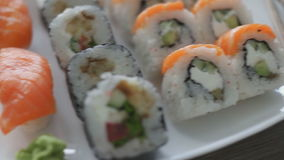 Various sushi on white plate. Japanese sushi on white plate with chopsticks on wooden background stock footage