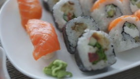 Various sushi on white plate. Japanese sushi on white plate with chopsticks on wooden background stock video