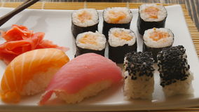 Various sushi on white plate on wooden background stock video footage