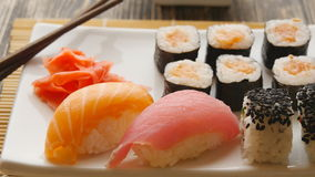 Various sushi on white plate on wooden background stock video