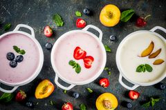Various sweet creamy fruit & berry soups. Strawberry, peach, blueberry, dark blue concrete background top view copy space royalty free stock photo
